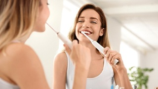 Young woman in white shirt using electric toothbrush