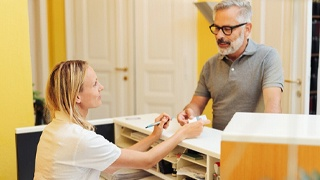 Mature man paying for treatment after emergency appointment