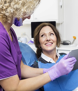 A middle-aged woman listening to her dentist explain the positive outcomes of having a root canal in Lakeville