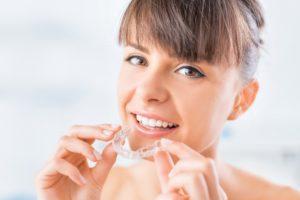 Smiling woman using SureSmile aligner to straighten teeth
