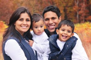 family of four smiling hugging