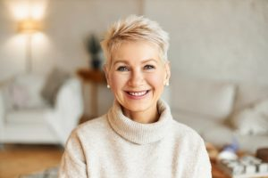 Older woman smiling while wearing a cream sweater
