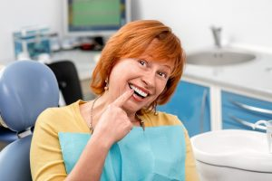 Happy patient pointing at her dental implants after tooth extraction